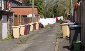 Household rubbish bins line an alleyway