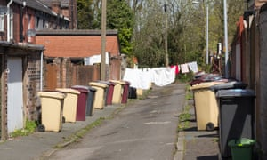 A back street, with washing drying on the line and bins outside, between two rows of terraced houses in Bolton Lancashire