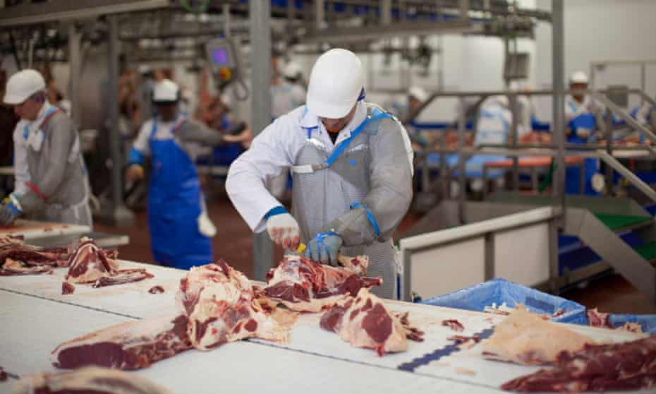 Butchers at work at a meat processing plant in the UK.