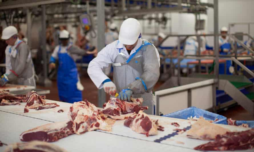 Butchers at work at a meat processing plant in the UK