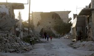 People walk past the rubble of damaged buildings in Maarat al-Nouman