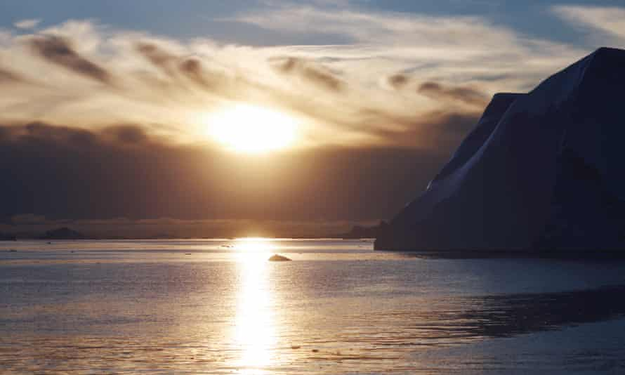 The sun sets beyond icebergs which calved from the Sermeq Kujalleq glacier float in the Ilulissat Icefjord in Ilulissat, Greenland