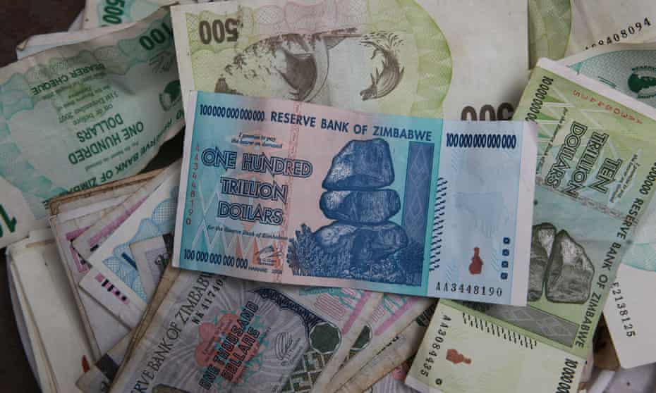 An  old 100 trillion Zimbabwean dollar note on top of a pile of other old Zimbabwean notes
