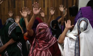 Female victims of sexual slavery covered in scarfs raise their hands at the verdict in the trial of two military officials in Guatemala City.
