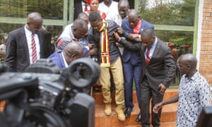 Bobi Wine is helped down steps before appearing at the general court martial in Gulu, northern Uganda, last month.