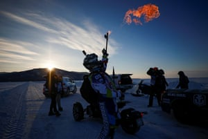 Maksimikha, Russia: a participant lights a torch during the Baikal Mile 2021 festival of speed on frozen Lake Baikal in the Buryatia republic