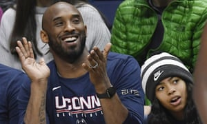 Kobe Bryant and his daughter Gianna watch the first half of an NCAA college basketball game between Connecticut and Houston in March 2019