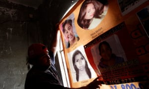 A man hangs up a banner showing photographs of missing and dead women in Ecatepec.