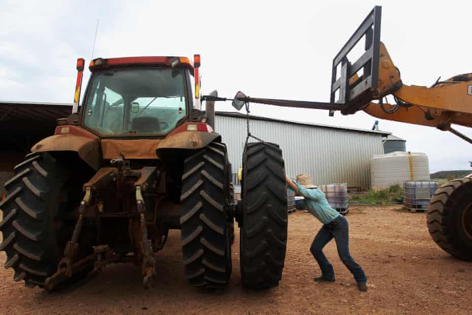 Jemima Penfold manoeuvres a tyre onto a tractor