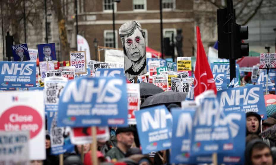 People take part in a march in London to demand more funds for the NHS