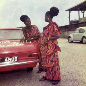 Two women talk while standing next to a red car