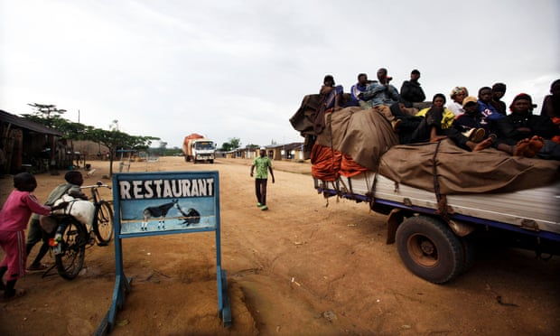A truck loaded with passengers stops outside a restaurant serving bush meat, in the town of Epulu, Democratic Republic of Congo.