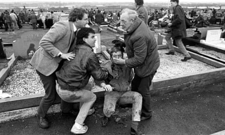 An injured man is aided by mourners