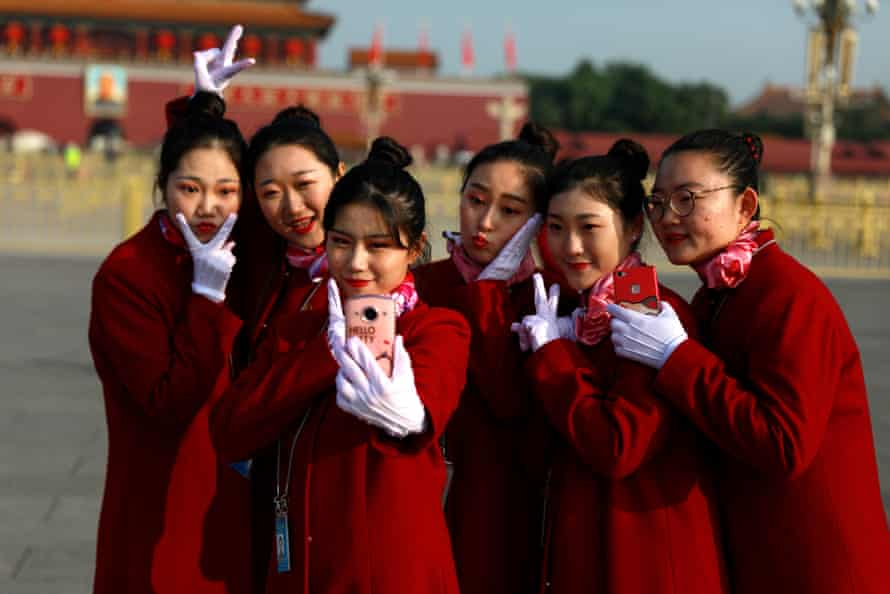 Hosts take selfies on Tiananmen Square before the closing ceremony of the 19th Communist party congress in Beijing