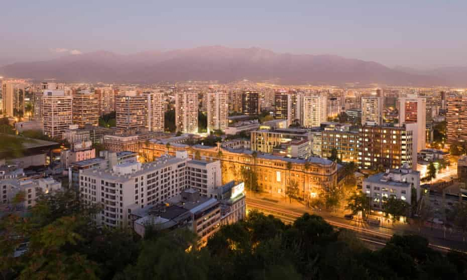 Santiago city skyline and the Andes mountains at dusk.