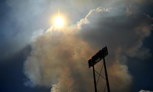 Smoke from the nearby bushfire drifts towards the ground.
