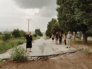 Anargyroi, Greece: Villagers from Anargyroi stand on the road towards the mine. Cracks from the landslide can be seen in the foreground. The road behind comes to an abrupt halt, with a steep drop where part of the village dropped into the mine