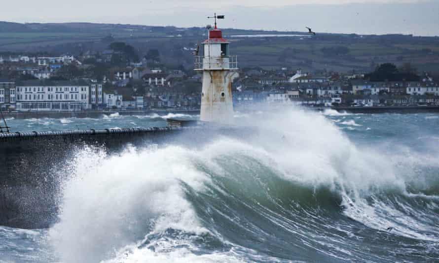 Waves crash against Newlyn pier