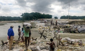 Locals gather building materials to build a dam as floodwaters flow from the north into Bihar near Muzaffarpur