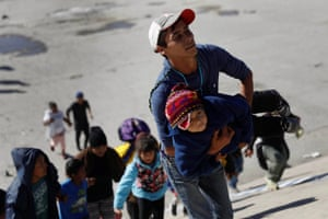 A migrant, part of a caravan of thousands traveling from Central America to the United States, holds his daughter after crossing the Tijuana river near the border wall between the US and Mexico.