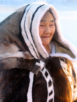 An elderly Inuit woman wearing traditional clothing made from caribou and seal skin, in Arctic Bay, Baffin Island, Nunavut, Canada