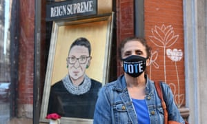 A woman poses in front of a painting of the late Ruth Bader Ginsburg near Union Square in New York City.