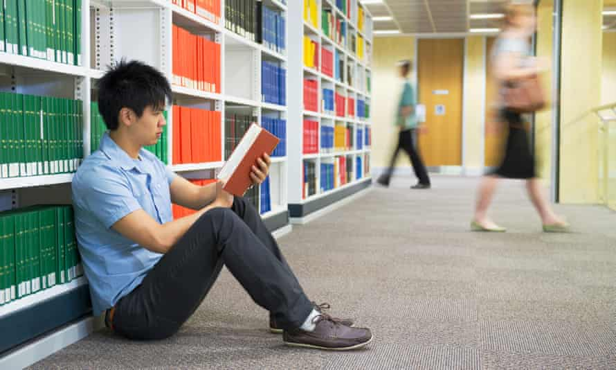 Chinese man reading book in library