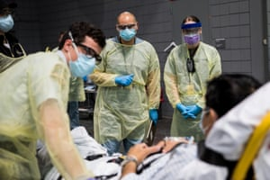 Soldiers assigned to Javits New York Medical Station conduct check-in procedures on an incoming coronavirus patient with local emergency workers in the facility's medical bay in New York City on 5 April.