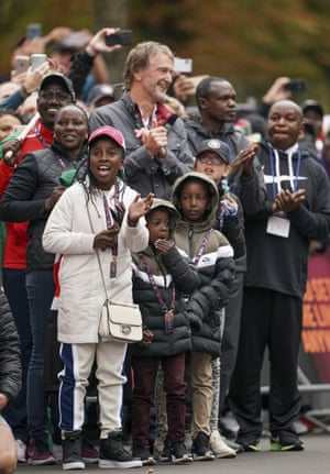 Kipchoge's wife, second left, children and Ineos chairman and CEO Sir Jim Ratcliffe, top, cheer him on.
