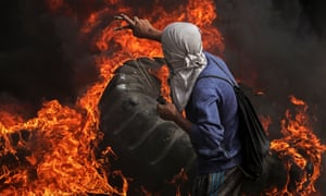 A Palestinian protester uses a slingshot to fire rocks over burning tyres along the border with Israel.