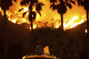 Six-year-old King Bass sits and watches the Holy fire burn from on top of his parents' car as his sister Princess, five, rests her head on his shoulder on 9 August in Lake Elsinore, California