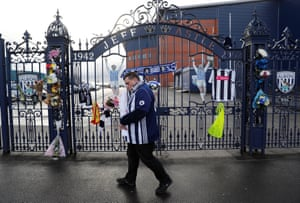 A fan leaves a tribute to Cyrille Regis at The Hawthorns.