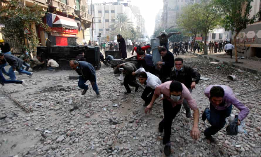 Protesters run for cover during clashes with the Egyptian riot police in Cairo, November 2011. Maspero saw repeated clashes during the revolution.