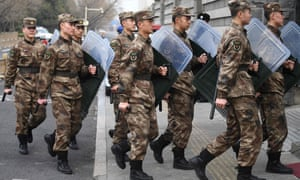 Liberation Army soldiers march to their barracks opposite the Great Hall of the People in Beijing on Friday. China is expected to decide whether to postpone its annual parliament session for the first time since the Cultural Revolution as the country battles the coronavirus outbreak.