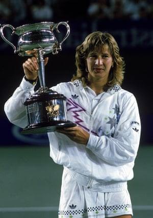 Becker's fellow German Steffi Graf raises the trophy after winning in 1988.