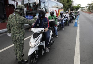 Police check the temperature of motorcyclists in Manila on Friday.