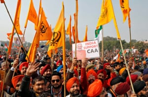 Supporters of India's ruling Bharatiya Janata Party hold flags as they attend a rally, addressed by Home Minister Amit Shah, in support of a new citizenship law on 21 January.