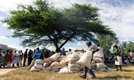 A man carries a full bag of donated maize grain in the Mutoko, Zimbabwe.