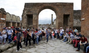Tourists stand on an ancient Roman cobbled street at Pompeii.