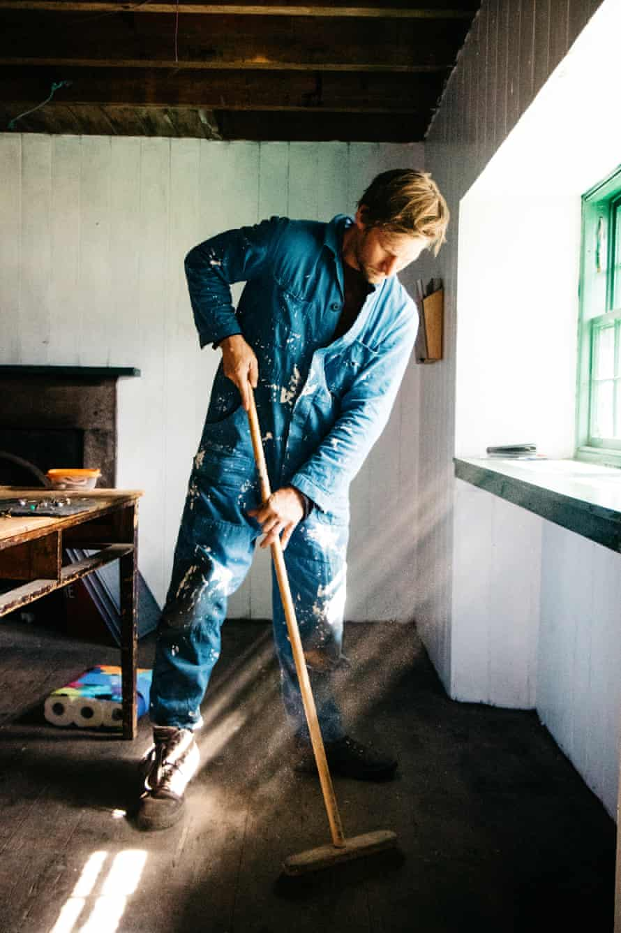 A younger volunteer sweeps up inside a bothy.