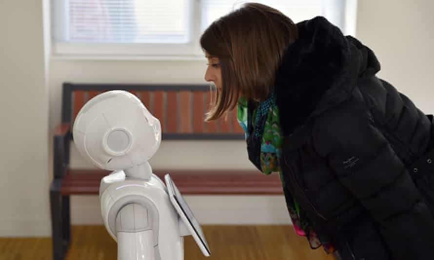 """TO GO WITH AFP STORY BY JEAN LIOU A woman interacts with """"Pepper"""", a humanoid robot which delivers information to users of the French railway company SNCF, on March 2, 2016 at the Nort-sur-Erdre train station, western France. Made by French firm Aldebaran, Japanese group SoftBank's subsidiary, Pepper has been installed in December 2015 in three stations in the Pays de la Loire region. / AFP / LOIC VENANCELOIC VENANCE/AFP/Getty Images"""