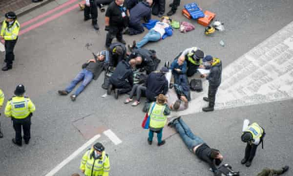Police officers try to remove activists lying in the road