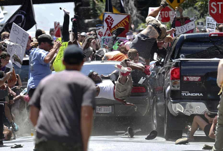 A vehicle drives into a group of protesters demonstrating against a white nationalist rally in Charlottesville, Virgina on 12 August 2017.