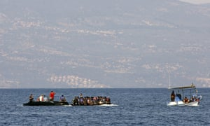 A fishing boat carries two dinghies of Syrian refugees to the Greek island of Lesbos