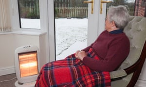 An elderly woman at home alone in front of an electric heater with a tartan blanket draped over her legs.