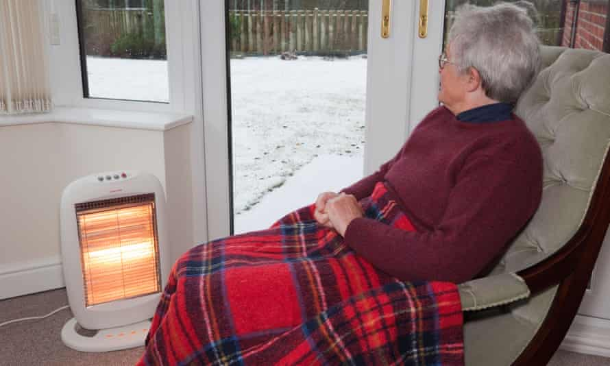 Older woman by electric fire with snow outside.