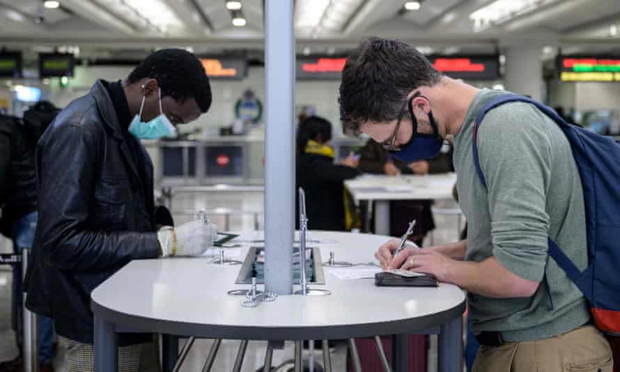 Passengers wearing face masks fill in health declaration forms at airport