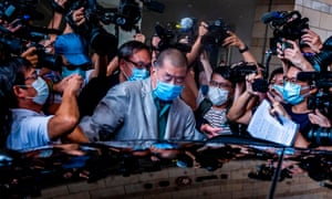 Jimmy Lai, centre, is besieged by photographers