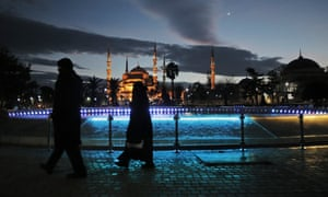 Tourists walk backdropped by the Sultan Ahmed Mosque, better known as the Blue Mosque, in the historic district.