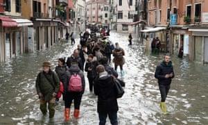 Tourists and locals wade through Venice's acqua alta.